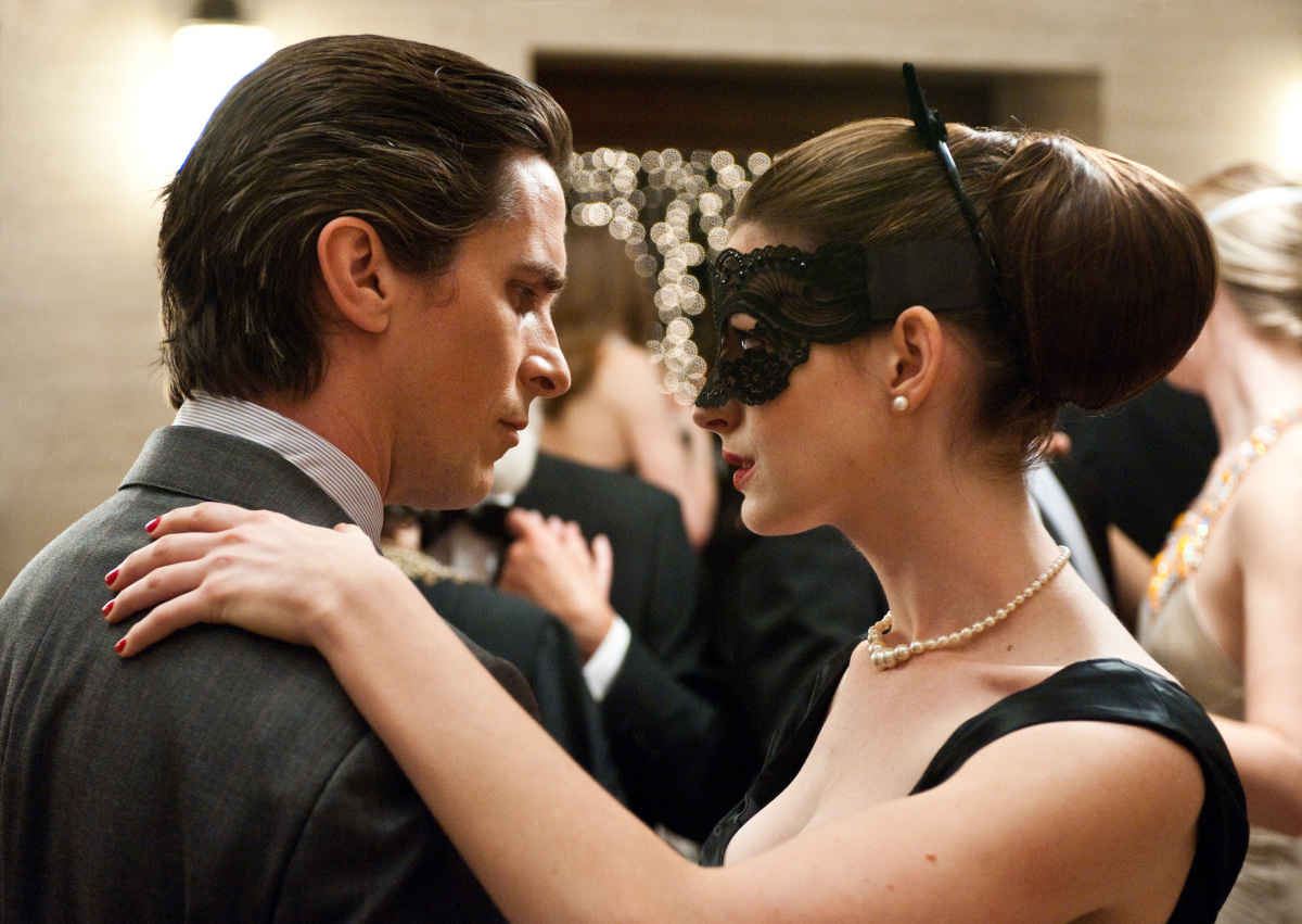 "Christian Bale as Bruce Wayne, left, and Anne Hathaway as Selina Kyle in a scene from the action thriller ""The Dark Knight Rises."" (Photo credit: AP Photo/Warner Bros. Pictures, Ron Phillips)"