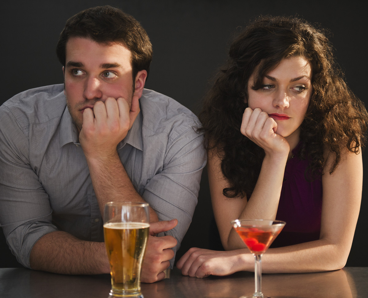Man and woman sitting at a bar ignoring each other