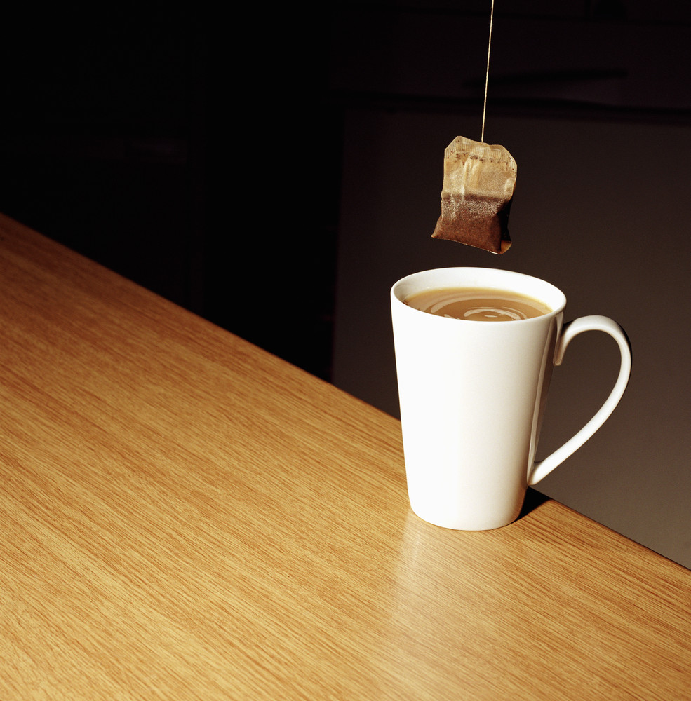 Teabag held over a cup