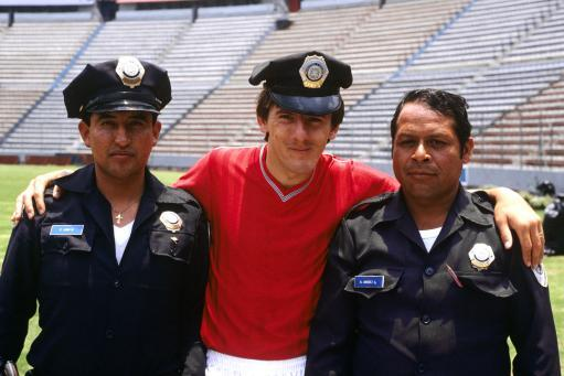 1986 - Peter Beardsley makes friends with two Mexican policemen. The two Mexican policemen don't look too happy about it.