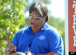 Steve McMichael autographs a football as he stands on the float at the
