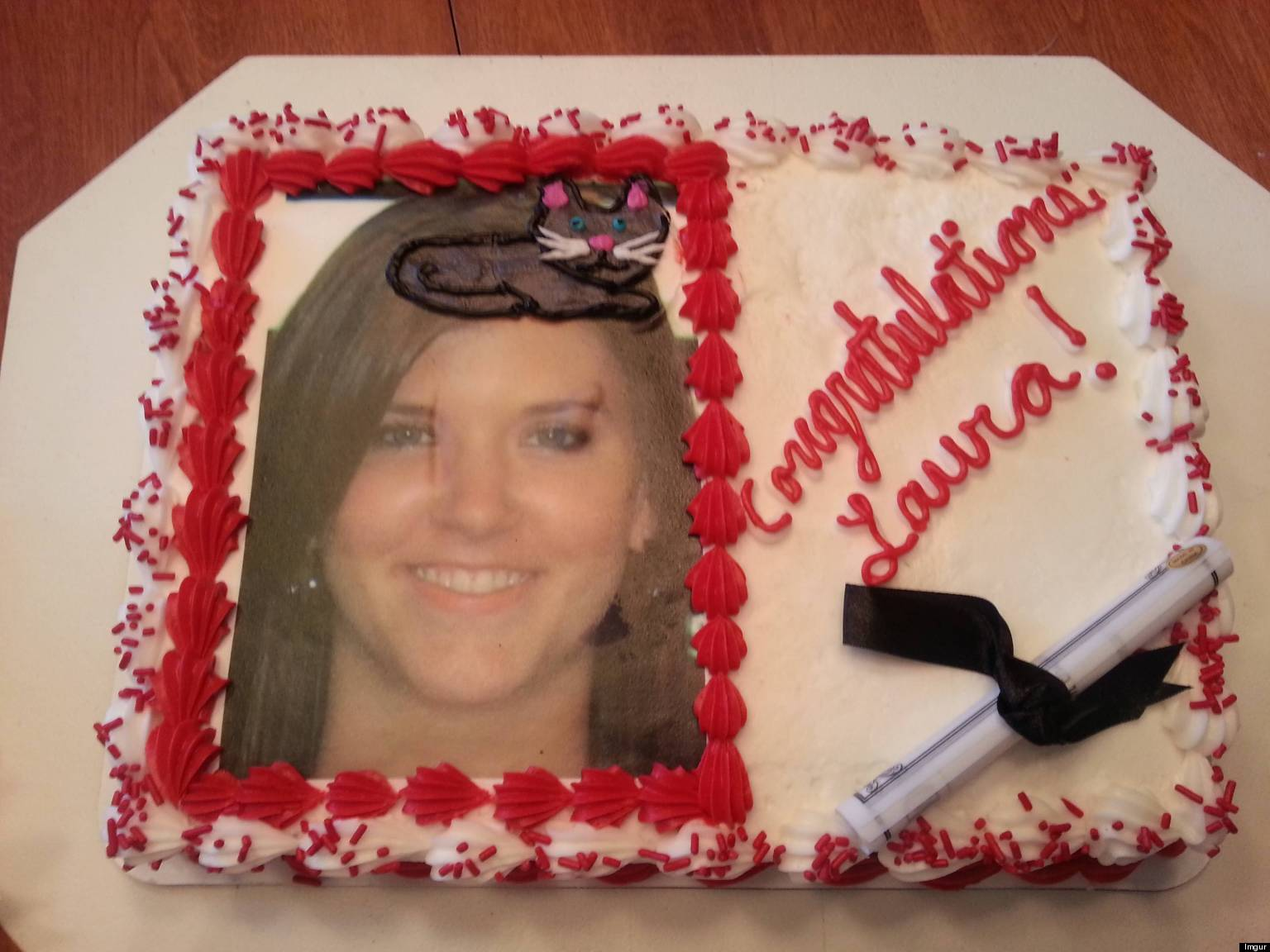 a photo of a cake with a womans smiling face on it. there is a cat on the op of her head
