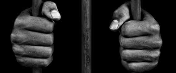HANDS OF A PRISONER ON PRISON BARS