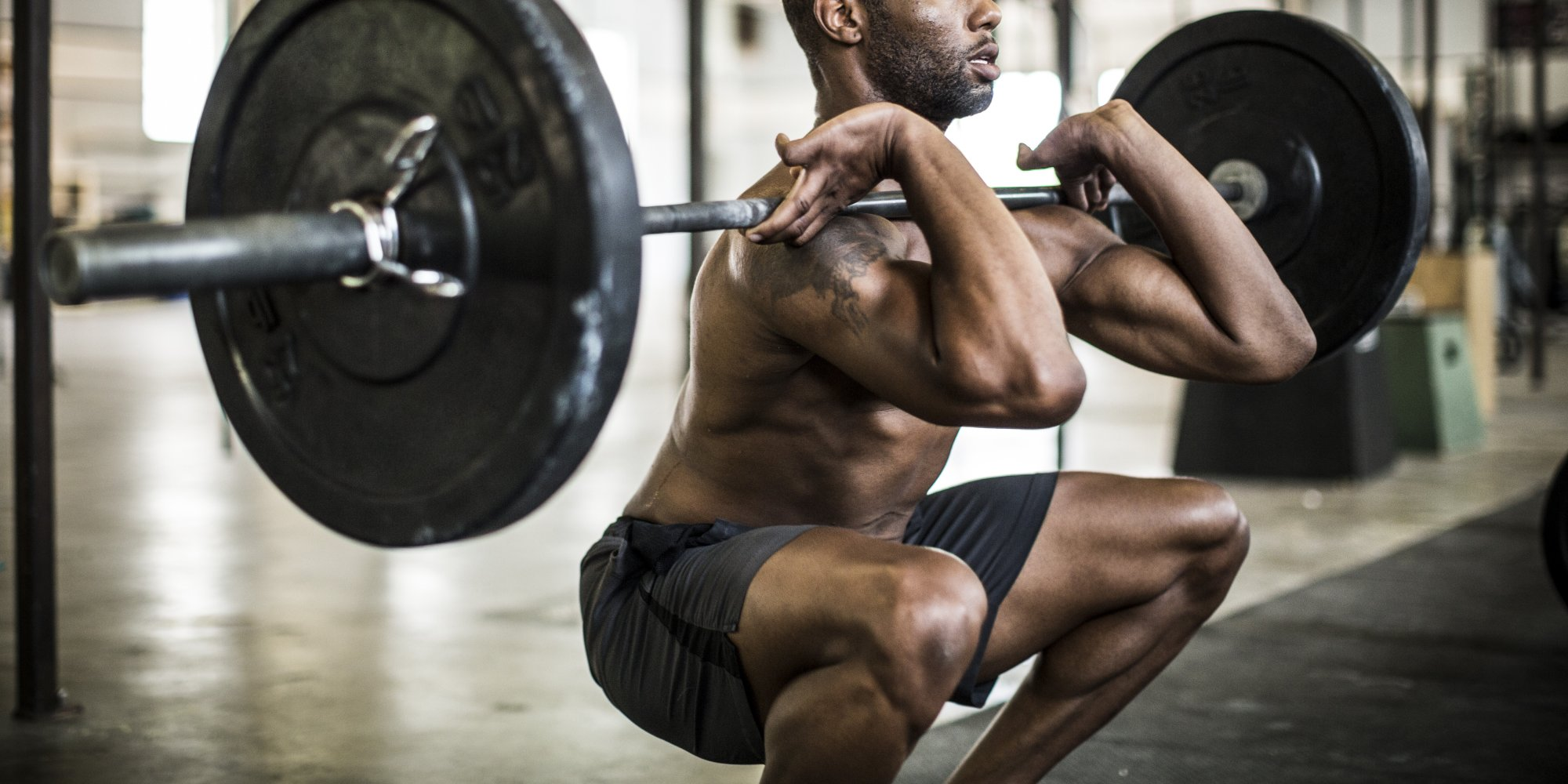 man doing a barbell squat with tempo training