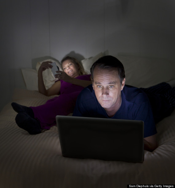 couple on computers in bed