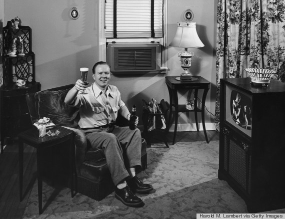 man in armchair watching television