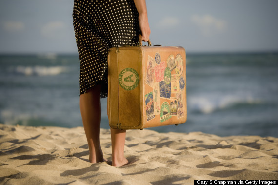 person standing on beach with luggage