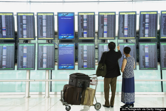 people looking at departures board airport