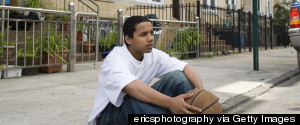 TEENAGER SITTING ON CURB