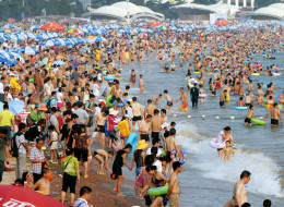 August 8, 2013 shows people gathering to cool off on a beach in Qingdao, east China's Shandong province, as a record-setting summer heat wave hit much of China. (Credit: STR/AFP/Getty Images) Click to enlarge.