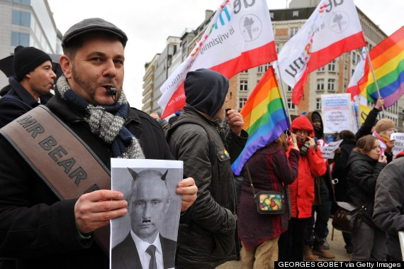a man holds a picture of russian president vladimi