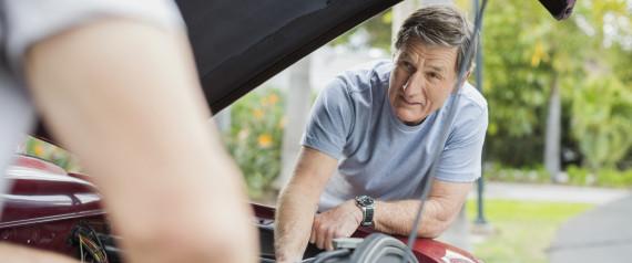older man fixing car