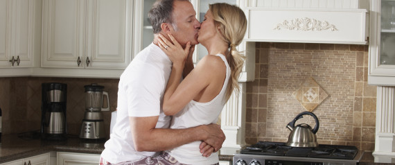 older couple kissing in kitchen