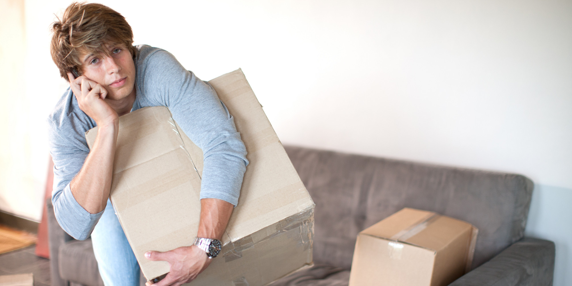 image of a man holding a box in the sofa