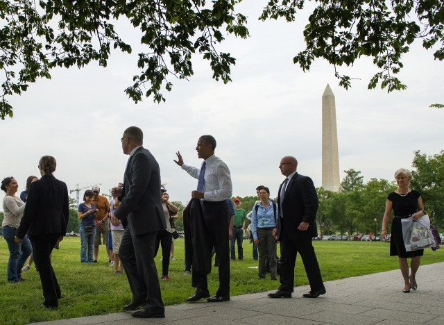 president barack obama waves to pedestrians