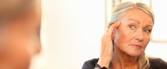 woman looking in mirror at wrinkles