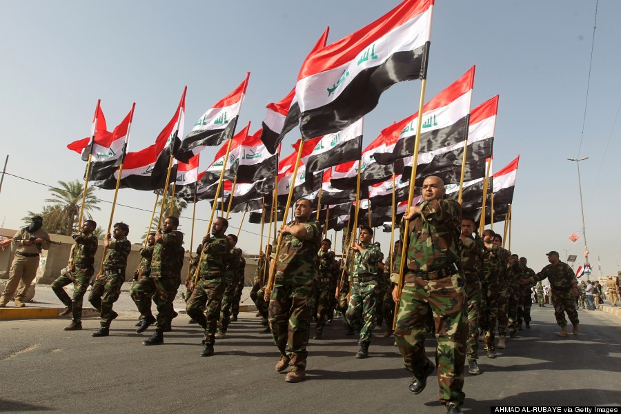 iraqi shiite fighters holding national flags