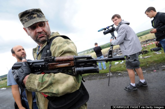 An armed pro-Russia militant attempts to stop journalists from accessing the site of the crash on July 19, 2014. (DOMINIQUE FAGET/AFP/Getty Images)