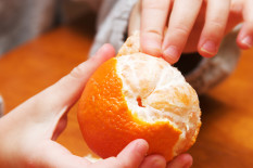 Orange being peeled | Pic: Getty
