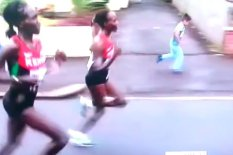 Child runs alongside marathon runner