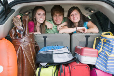 Family in car with suitcases, posed by models