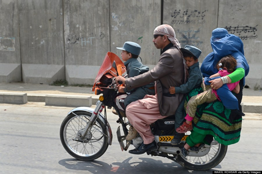 an afghan family travelling by motorcycle in kabul
