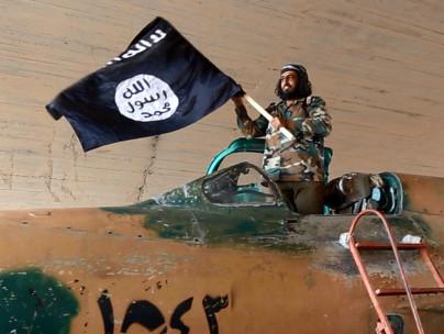 ISIS militant waves a flag in Raqqa