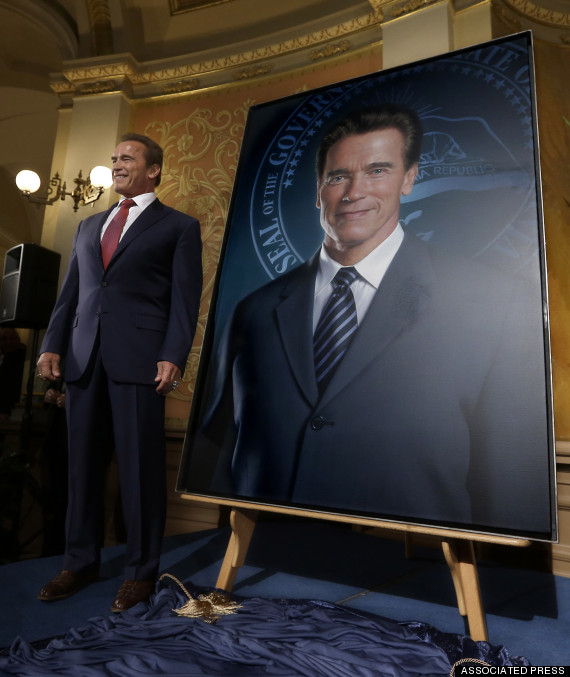 Arnold Schwarzenegger posing with his portrait