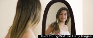 TEENAGE GIRL LOOKING IN MIRROR