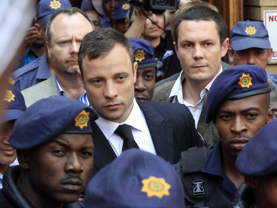 Oscar Pistorius flanked by police officers