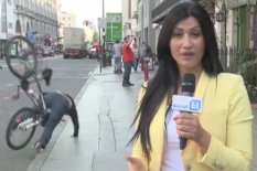 TV reporter on air, with man falling off bike in background | Pic: YouTube