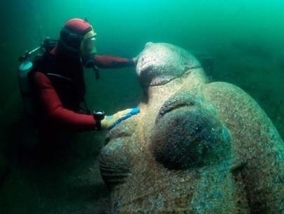 Diver examining statue underwater