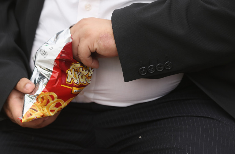 Obese man eating crisps