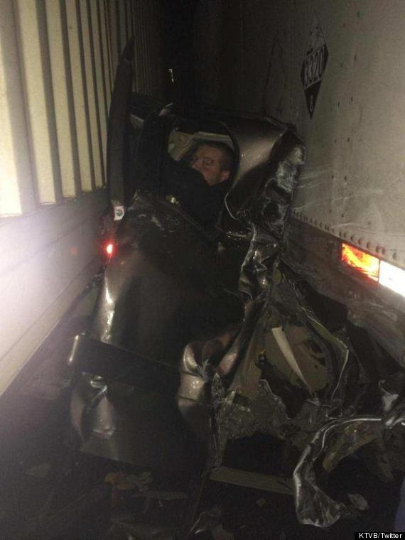 man sandwiched between trucks