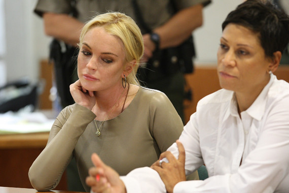Lindsay Lohan in court with her lawyer looking at her writing down something.