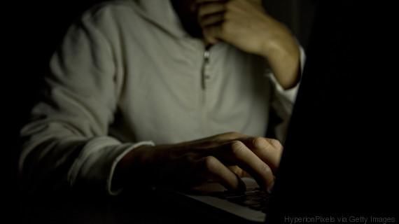 man sat computer dark