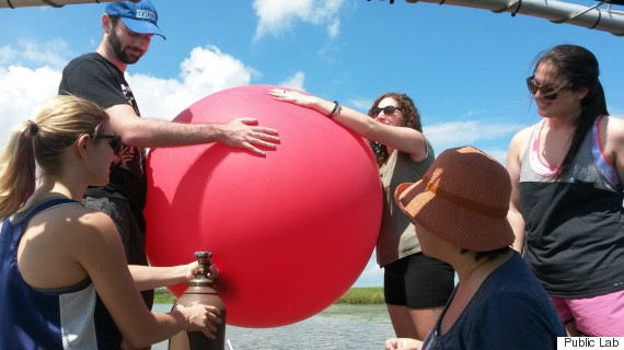 picture of activist group preparing a big red balloon for aerial surveillance of environmental problems.