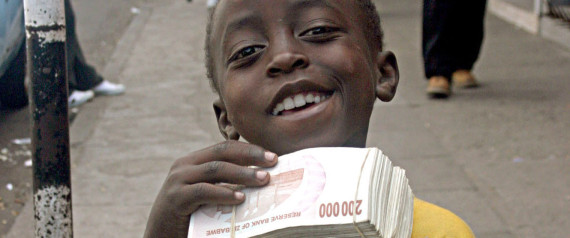 A CHILD POSES WITH WADS OF ZIMBABWEAN