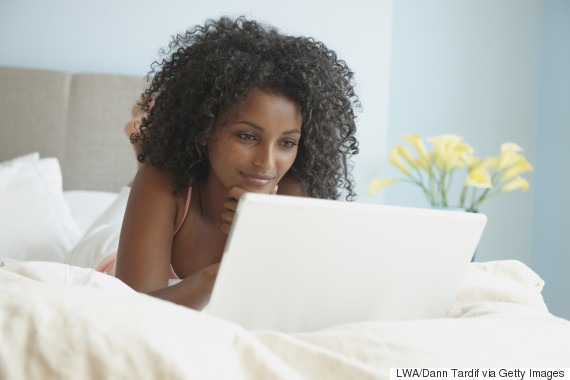 black woman computer bed