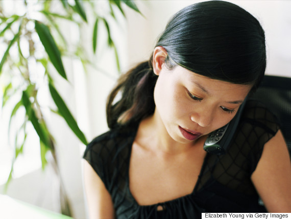 asian woman on phone serious