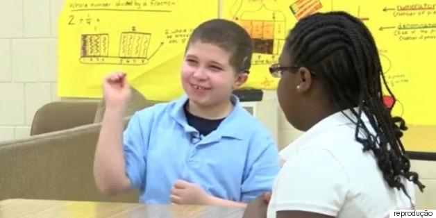 Crianças usam intervalo da aula para aprender sinais e conversar com colega surdo