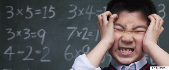 frustrated schoolboy in front of blackboard