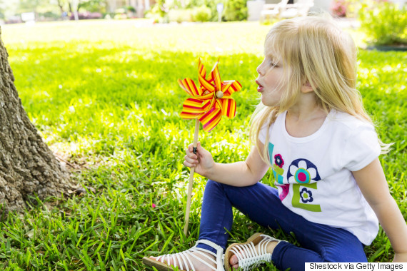 child blowing pinwheel