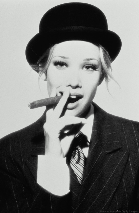 woman wearing suit hat smoking