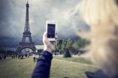 Woman using phone in Paris | Pic: Getty Images
