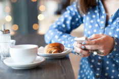 Woman using phone at breakfast | Pic: Getty Images