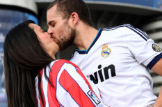 A Real Madrid fan kissing an Atletico fan before the game