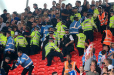 Police and stewarts hold back fans | Pic: PA