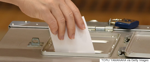 a woman casts her ballot at a polling station in t