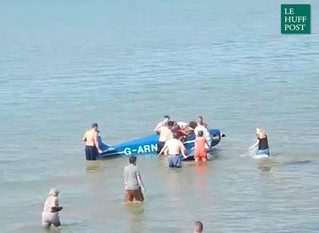 Des baigneurs sortent un pilote de son avion écrasé sur la plage